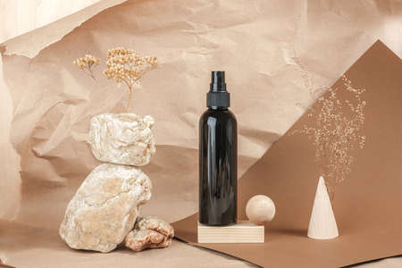 Brown bottle of cosmetic products on stone, wooden geometric shapes on beige paper background. Natural Organic Spa Cosmetic Beauty concept Front view.