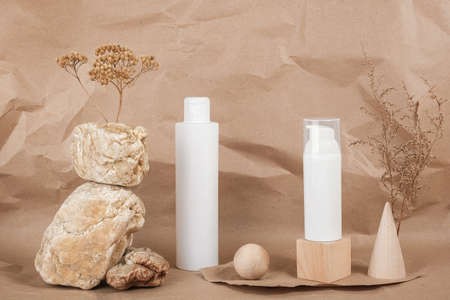 Two white blank cosmetic bottles with cream, serum or other cosmetic product, stones, geometric shape, dried plant flowers on beige background. Natural Organic Spa Cosmetic. Beauty concept.