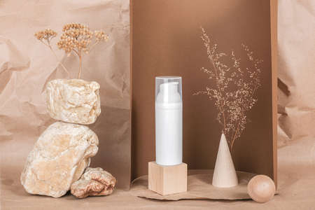 White blank cosmetic bottle with cream, moisturizer or other cosmetic product, stones, dried plant flowers on brown background. Natural Organic Spa Cosmetic. Beauty concept. Front view.