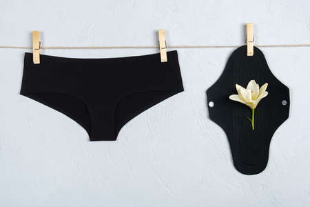 Eco sanitary reusable pad with white delicate flower and black underpants on washing line, gray background. Health care and zero-waste, no plastic concept. 免版税图像