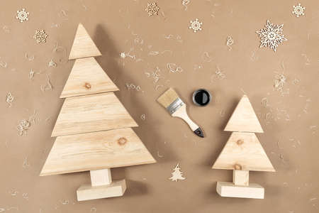XMAS or New Year composition. Handmade wooden Christmas trees, paint, brushes on craft beige background. Concept Zero waste, eco - friendly Merry Christmas. Top view Flat lay. 免版税图像