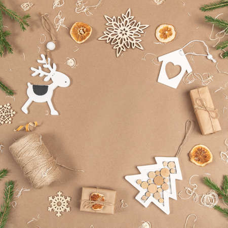 XMAS or New Year composition. Frame, border made from boxes, twine, wood decoration, dried oranges and spruce branches on craft beige background. Concept Zero waste Merry Christmas Copy space.