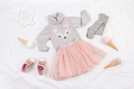 Set of casual child clothes, shoes and accessories on white background. Fashion girl lookbook consept. Knitted sweater, tulle skirt, sneakers, tights, ice cream cone. Top view, flat lay.