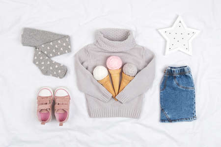 Set of casual child clothes, shoes and accessories on white background. Fashion girl lookbook consept. Knitted sweater, denim skirt, sneakers, ice cream cone. Top view, flat lay.