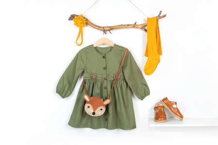 Set of stylish child clothes. Hanger with green dress, brown bag and yellow tights, accessories for hair on wooden stick, shoes on shelf. Fashion girl lookbook concept, Front view.