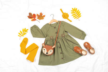 Stylish autumn set of child clothes. Green dress, brown bag, shoes and yellow tights, accessories for hair and autumn leaves on white background. Fashion girl lookbook concept.Top view Flat lay. 免版税图像