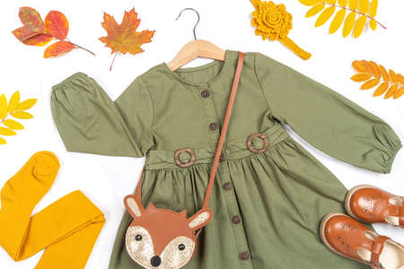 Stylish autumn set of child clothes. Green dress, brown bag, shoes and yellow tights, accessories for hair and autumn leaves on white background. Fashion girl lookbook concept.Top view Closeup. 免版税图像