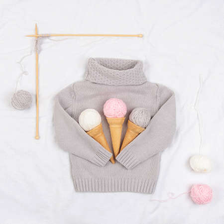 Three ice cream from yarn and waffle cones on a gray knitted sweater, wooden knitting needles on white background. Knitting, hobby and handmade concept. Top view Flat lay. 免版税图像