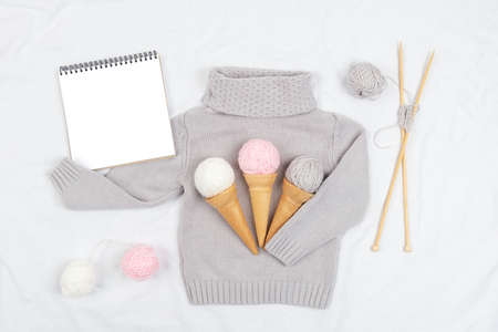 Three ice cream from yarn and waffle cones on a gray knitted sweater, wooden knitting needles and open notepad on white background. Knitting, hobby and DIY concept. Top view Flat lay.