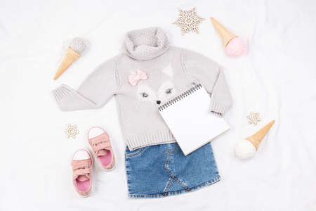 Set of casual child clothes, shoes, accessories and open notepad on white background. Fashion girl lookbook consept. Knitted sweater, denim skirt, sneakers, ice cream cone. Top view, flat lay Mockup. 免版税图像