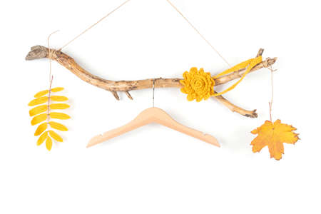 One hanger on a thick wooden stick and fall yellow leaves, great design for any purposes. Concept Season autumn sale or Eco-Friendly Homes. Front view.