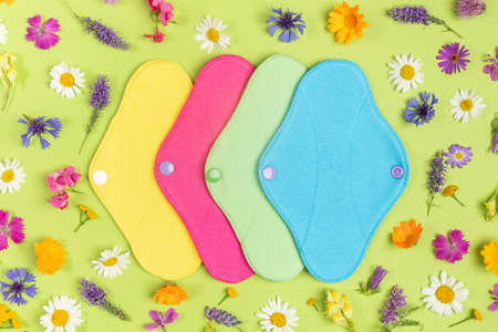 Colored reusable menstrual pads on green background with natural colorful wild flowers. Health care and zero-waste, no plastic, eco-friendly concept. Top view Flat lay. 免版税图像