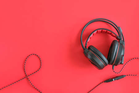 Black headphones on red background. Concept listening to audio material and abstract, distance education. Top view copy space. 免版税图像