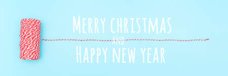 Merry christmas and Happy new year banner. Skein of red and white twine for packing gifts, boxes, parcels on blue background. Holiday concept. Minimal style Top view.