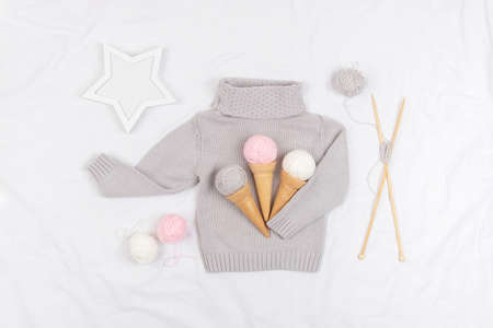 Three ice cream from yarn and waffle cones on a gray knitted sweater, wooden knitting needles and star on white background. Knitting, hobby and handmade concept. Top view Flat lay. Zdjęcie Seryjne