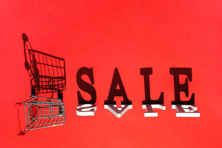 Word SALE, empty shopping trolley cart and shadow on red background. Concept Black friday and sale. Creative template for your design, ad or advertisement.