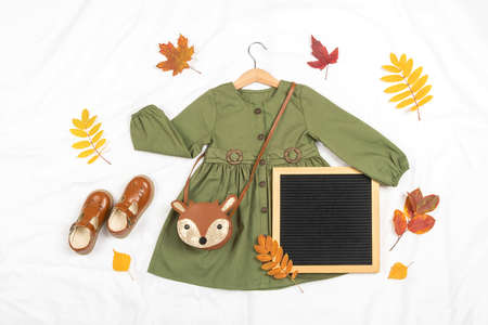 Stylish autumn set of child clothes. Green dress, brown bag, shoes, letter board frame and autumn leaves on white background. Fashion girl lookbook concept. Mockup Top view Flat lay. Zdjęcie Seryjne
