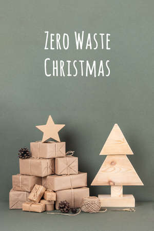 Zero Waste Christmas text. Homemade wooden Christmas tree, a lot gift, holiday decor on green background. Concept eco-friendly, no plastic Xmas or New Year holiday. Front view. Zdjęcie Seryjne