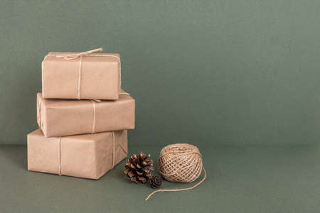 Three boxes in craft paper, twine and cones on green background. Concept XMAS or New Year holiday, Zero waste Merry Christmas. Front view Copy space.