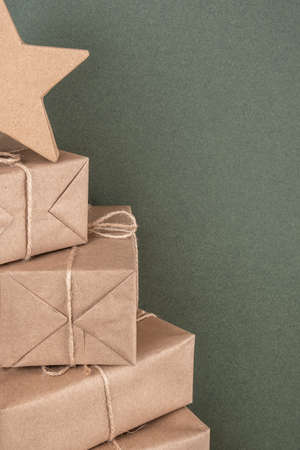 Christmas tree. Boxes in craft paper on green background, closeup. Concept XMAS or New Year holiday. Front view Copy space.