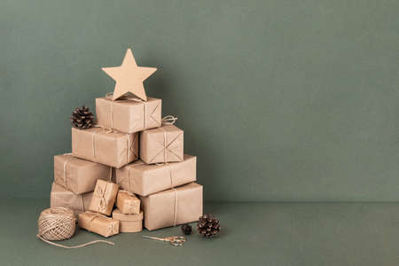 Abstract Christmas tree. Boxes in craft paper, twine, scissors, cones on green background, closeup. Concept XMAS or New Year holiday. Front view Copy space. Archivio Fotografico