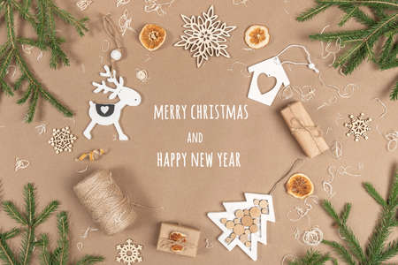 XMAS or New Year postcard. Frame, border made from boxes, twine, wood decoration, dried oranges and spruce branches on craft beige background. Concept Zero waste Merry Christmas Copy space. 免版税图像