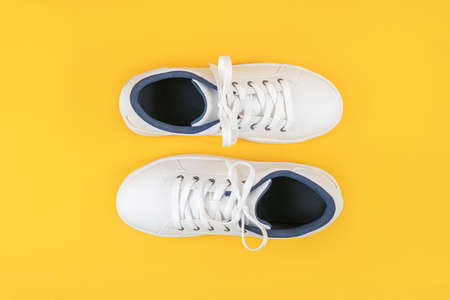 White sports shoes, sneakers with shoelaces on a yellow background. Sport lifestyle concept Top view Flat lay. 免版税图像