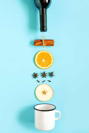 Mulled Wine Ingredients, still life on blue background. Bottle of wine, cinnamon sticks, slices of orange, apple, anise and mug. Concept culinary recipe holiday drink Creative Top view Flat lay.