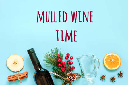 Mulled Wine Ingredients, still life on blue background. Bottle of wine, cinnamon sticks, slices of orange, apple, anise and mug. Concept culinary recipe Creative Top view Flat lay Copy space.