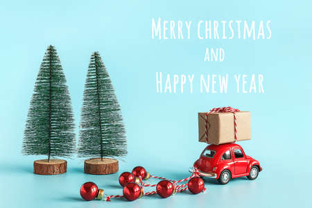 Small red car carries gift box and christmas tree with copy space. Concept Happy new year and Merry christmas. Template for design, postcard, invitation. Novosibirsk, Russia - October 20, 2019. 新闻类图片