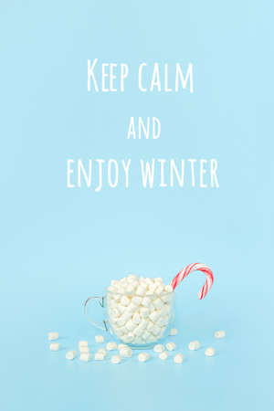 Keep calm and Enjoy winter, motivational quote. Big transparent cup of marshmallows with red lollipop cane on blue background. Concept inspirational quote Front view, Greeting card.