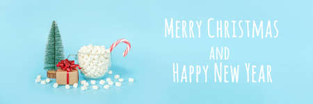 Merry christmas and Happy new year postcard. Gift box, christmas tree and cup of marshmallows with red lollipop cane on blue background. Holiday concept. Front view, Banner. 免版税图像