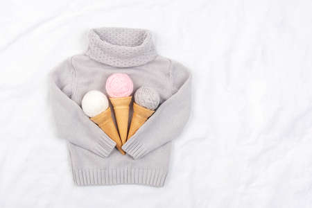 Three ice cream from ball of yarn in waffle cones and gray knitted sweater on white background. Top view Flat lay Copy space. 免版税图像