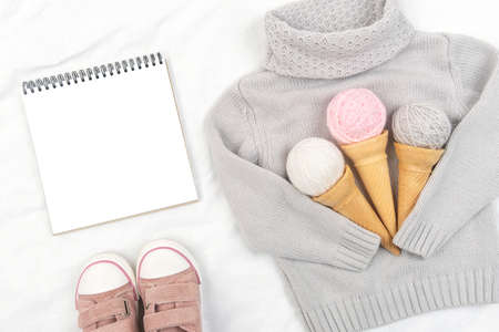 Three ice cream from yarn in waffle cones on gray knitted sweater, pink sneakers and open notepad on white background. Top view Flat lay Mockup.