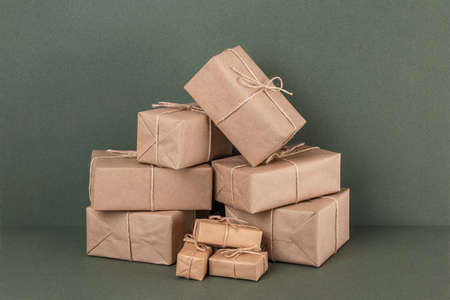 Lots of gifts boxes in craft paper with twine on green background. Holiday concept. Front view. Stockfoto