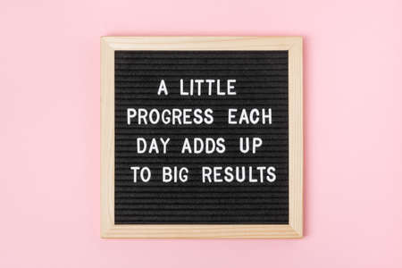 A little progress each day adds up to big results. Motivational quote on black letter board on pink background. Concept inspirational quote of the day. Greeting card, postcard. 免版税图像