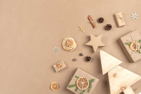 Xmas composition. Homemade wooden Christmas tree, gifts, holiday decor on craft beige background. Concept christmas zero waste, eco-friendly. Top view Flat lay Copy space. 免版税图像