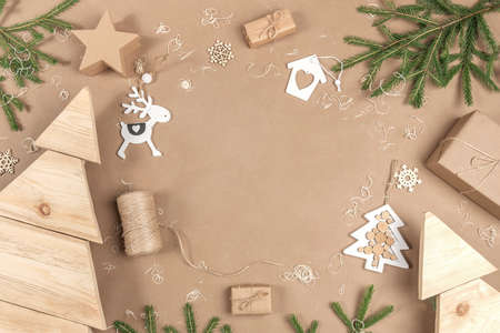 XMAS or New Year composition. Frame, border made from boxes, twine, wood decoration and spruce branches on craft beige background. Concept Zero waste Merry Christmas Copy space. 免版税图像