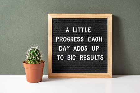A little progress each day adds up to big results. Motivational quote on letter board, cactus, succulent flower on white table. Concept inspirational quote of the day. Front view.