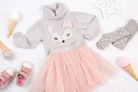 Set of casual child clothes, shoes and accessories on white background. Fashion girl lookbook consept. Knitted sweater, tulle skirt, sneakers, tights, ice cream cone. Top view, flat lay, Closeup.