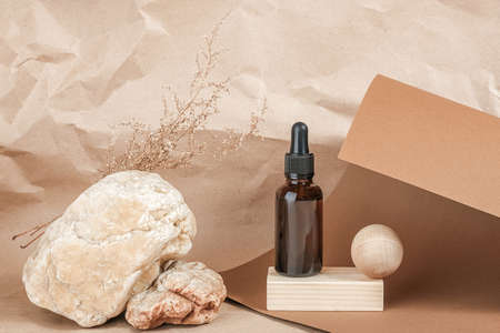 Brown glass bottles of cosmetic products on stone and wooden geometric shapes on beige craft paper background. Natural Organic Spa Cosmetic Beauty concept Front view Mockup.