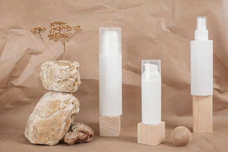 Three white blank cosmetic tube with cream, lotion or shampoo, stones, geometric shape, dried plant flowers on beige craft paper background. Natural Organic Spa Cosmetic. Stock fotó