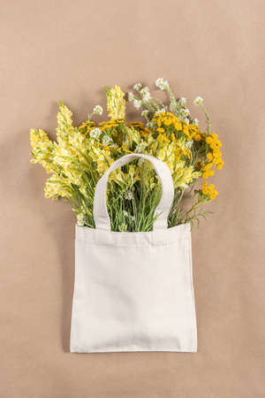 Bouquet of field flowers in fabric eco bag on beige background. Concept no plastic and zero waste. Top view Mockup.