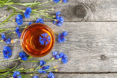 Cup of herbal tea and blue cornflowers flowers on wood background. Top view Flat lay Copy space
