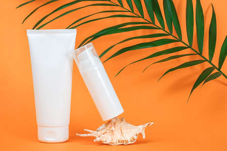 Two white blank cosmetics bottles with sunscreen, suncream or other cosmetic product, seashell and green brunch palm on orange background. Concept skin care in summer holiday Mockup Front view. Stock fotó
