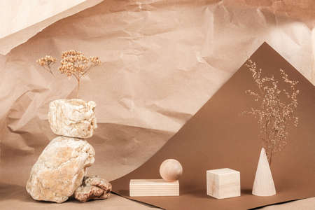 Creative podium for cosmetics or you merchandise, products. Layout made of from wooden geometric shapes, stones and dried flowers on brown beige paper background. Stock fotó