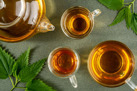 Cups of herbal tea, transparent teapot and nettle leaves on green background. Top view Flat lay. Stock fotó
