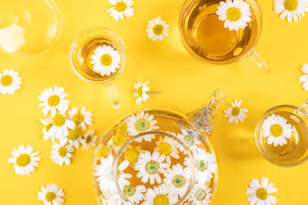 Three cups of tea and transparent teapot with camomile flowers on yellow background. Chamomile Tea Benefits Your Health concept. Top view Flat lay. Stock fotó