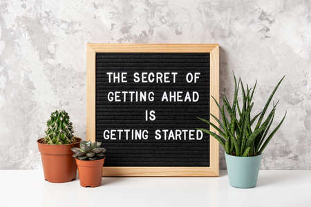 The Secret Of Getting Ahead Is Getting Started. Motivational quote on letter board, cactus, succulent flower on white table. Concept inspirational quote of the day. Front view. Stock fotó