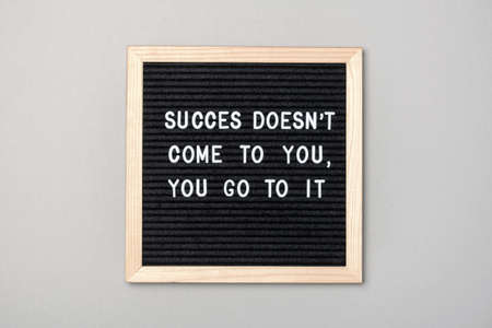 Success doesn't come to you, you go to it. Motivational quote on black letter board on gray background. Concept inspirational quote of the day. Greeting card, postcard.
